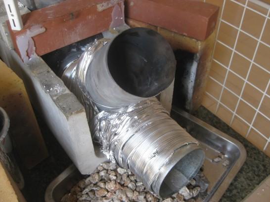 ロケットストーブの燃焼室の周りはアルミダクトや小石で簡易的な断熱を施す