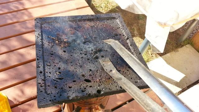 炭ばさみで溶岩プレートの焼け残りを掃除